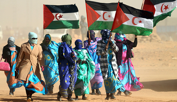 Sahrawi women hold Polisario Front's flags during a ceremony to mark 40 years after the Front proclaimed the Sahrawi Arab Democratic Republic (SADR) in the disputed territory of Western Sahara on February 27, 2016 at the Sahrawi refugee camp of Dakhla which lies 170 km to the southeast of the Algerian city of Tindouf.  SADR was declared in 1976 by the Polisario Front -- a rebel movement that wants independence for Western Sahara -- which fought a guerrilla war against Rabat's forces before a ceasefire in 1991.  / AFP / Farouk Batiche        (Photo credit should read FAROUK BATICHE/AFP/Getty Images)